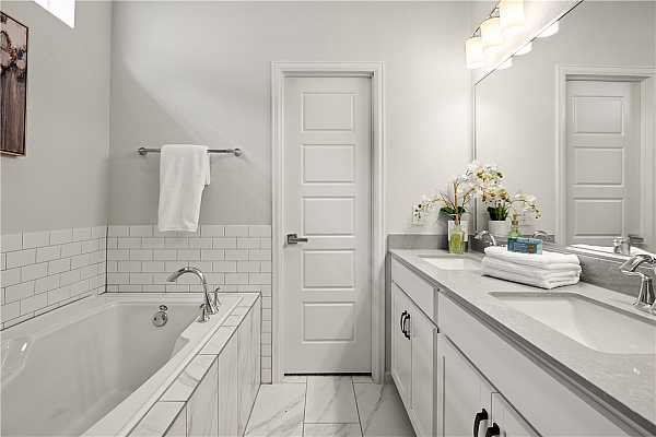 Photo #28 Primary bath with double vanities, quartz counters and a garden soaking tub.