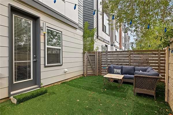 Photo #9 Step outside to your own private backyard, fully enclosed and covered in artificial turf.