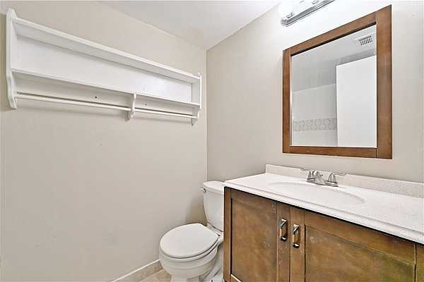 Photo #27 A full bathroom just down the hall features a vanity with storage, a bath/shower combo, and additional open shelving.
