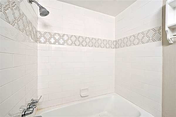 Photo #28 The shower is detailed with patterned tilework, bringing an aesthetic flair to the space.