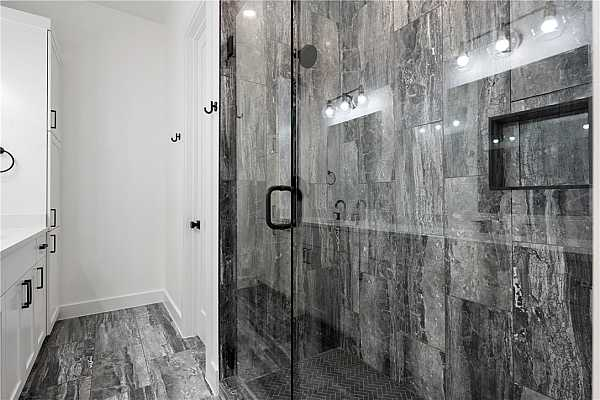 Photo #17 Sleek porcelain tiles continue from floor to shower walls.