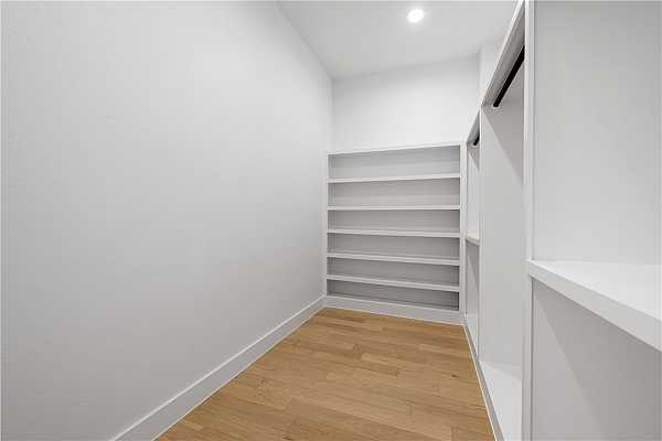 Photo #18 Primary walk-in closet with custom built-ins.