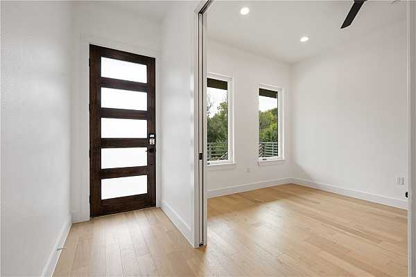 Photo #2 View of five-panel glass solid wood door and main level bedroom/office.