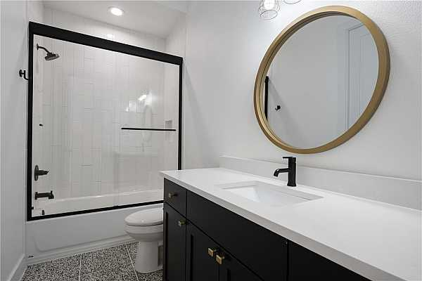Photo #5 Main level bath featuring Terrazo 16 X 16 polished tiles, custom metal frame shower door with sliding glass panels and Delta fixtures. Mirror is included.