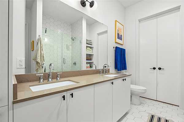 Photo #16 Double vanity with floor to ceiling storage cabinet.